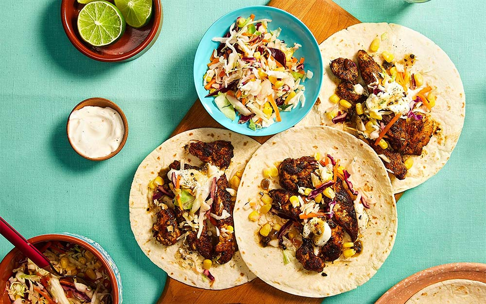 Spicy Jerk Chicken Tacos with a sweet corn and lime slaw,