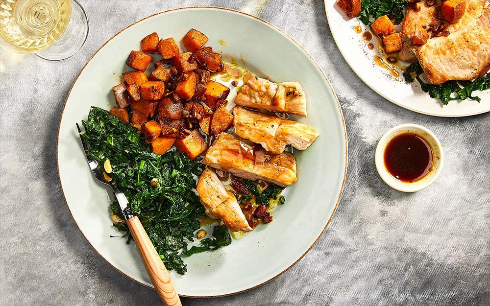 Maple Cider Pork Chops with garlic kale and pecan sweet potatoes,