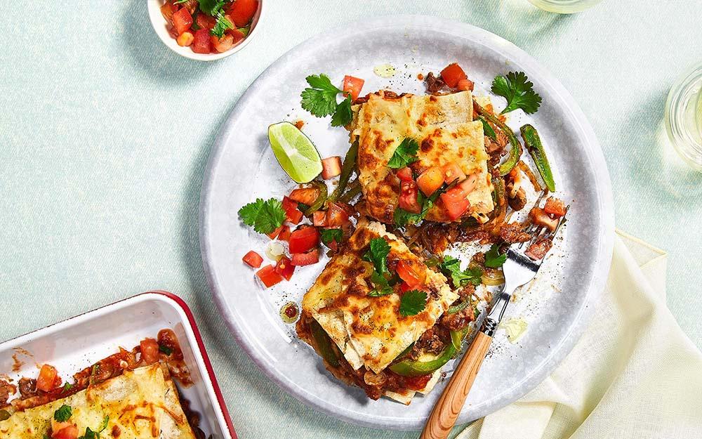 Cheesy Enchilada Bake with creamy layered beans and tomato salsa,