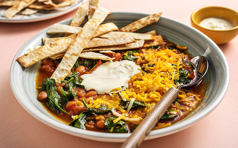 Tortilla Soup with beans, tomatoes and cheese,
