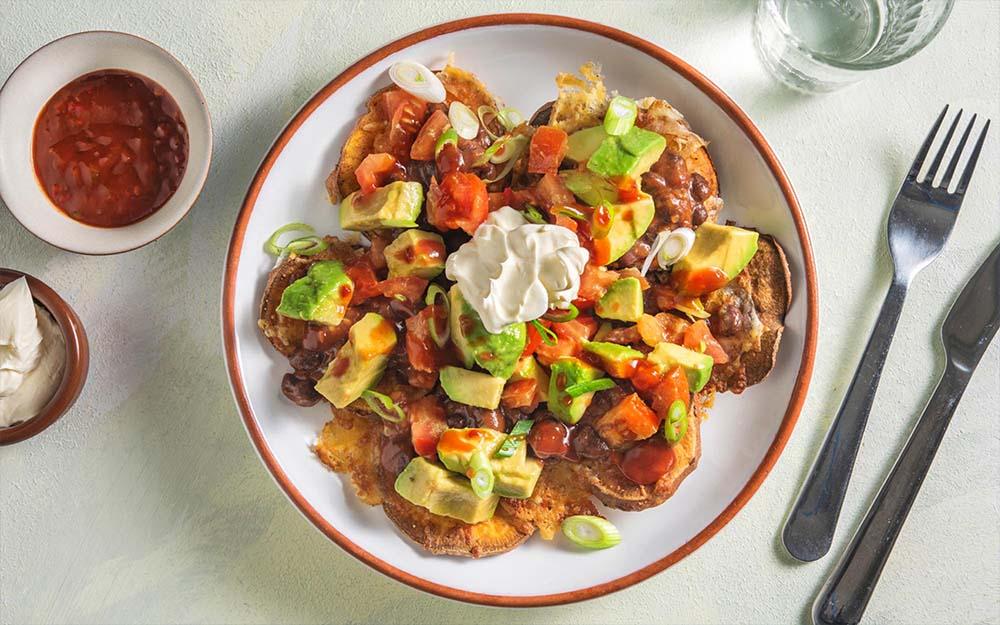 Sheet Pan Sweet Potato Nachos with tomato salsa and sour cream,